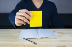 Note collante se tenant par la main de l'homme, se reposant sur le bureau en bois de travail photographie stock