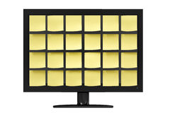 Note Covered Monitor on Desk. Sleek modern computer monitor covered in organized yellow notes in front of a white background Royalty Free Stock Photos