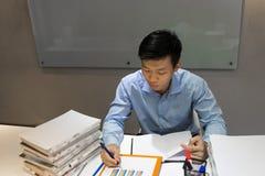 Note d'écriture de jeune homme dans le rapport de ventes image libre de droits