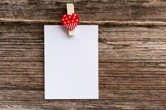 Note de blanc de papier de pince à linge de coeur Image stock