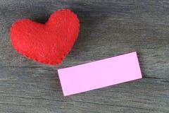 Note de coeur rouge et de papier blanc placée sur un plancher en bois Images stock