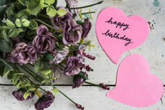 Note de joyeux anniversaire en papier de forme de coeur avec les fleurs pourpres Photographie stock