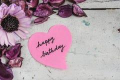 Note de joyeux anniversaire en papier de forme de coeur avec les fleurs roses Photo libre de droits