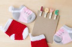 Note de papier blanc avec des agrafes d'amour et des chaussettes de bébé sur le backgr en bois Image stock