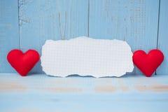 Note de papier blanc avec la décoration rouge de forme de coeur de couples sur le fond en bois bleu de table Valentine' l'épous images libres de droits