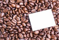 Note de papier blanc sur les grains de café rôtis Images stock