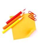 Note de papier collante orange avec les clips et les crayons rouges Photos stock