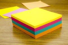 Note de papier d'autocollant sur le fond en bois Formules en blanc pour des notes de travailleurs illustration 3D Photos stock