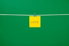 Note de papier jaune sur la corde à linge avec amour des textes Images libres de droits