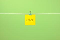 Note de papier jaune sur la corde à linge avec amour des textes Photos libres de droits