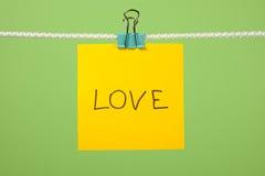Note de papier jaune sur la corde à linge avec amour des textes Photo stock
