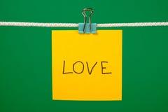 Note de papier jaune sur la corde à linge avec amour des textes Photographie stock libre de droits