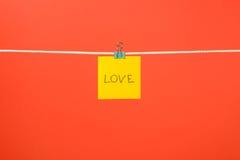 """Note de papier jaune sur la corde à linge avec le  d'""""Love†des textes Photos stock"""