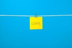 """Note de papier jaune sur la corde à linge avec le  d'""""Love†des textes Images libres de droits"""