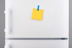 Note de papier jaune vide et autocollant bleu sur le réfrigérateur blanc Images libres de droits