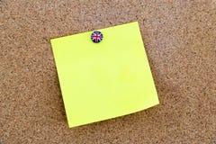 Note de papier jaune vide goupillée avec la punaise de drapeau de la Grande-Bretagne Image libre de droits