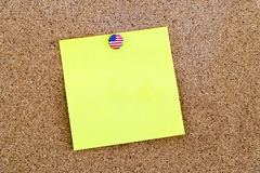 Note de papier jaune vide goupillée avec la punaise de drapeau des Etats-Unis Images stock