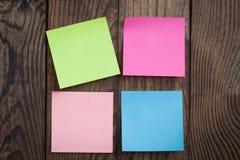 Note de papier multicolore d'autocollants sur en bois Photographie stock libre de droits