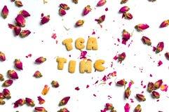 Note de temps de thé et fleurs roses de thé sur le blanc Image stock