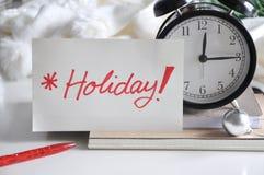 Note de vacances mise en Front Alarm Clock Photographie stock libre de droits