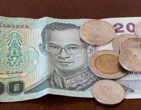 Note de vingt bahts de Thaïlande avec des pièces de monnaie Image stock