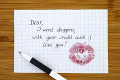 Note - Dear, I went shopping with  your credit card. Love you! w. Ith kiss and pen. Wooden background Stock Images