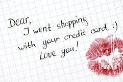 Note - Dear, I went shopping with your credit card. Love you! wi. Th kiss on paper. Close-up Stock Image