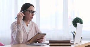 Note della lettura della donna di affari e discutere sulla videoconferenza facendo uso del computer portatile archivi video