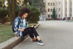 Note della lettura della giovane donna allo spazio della copia dell'università Fotografie Stock