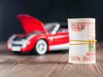 Note della rublo su fondo toycar con un cappuccio alzato Fotografia Stock