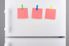 Note di carta rosa allegate con gli autoadesivi sul frigorifero bianco Immagini Stock