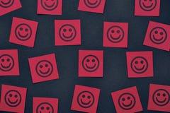 Note di carta rosse con i fronti felici Fotografia Stock