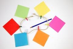 Note di Post-it con i piccoli pioli colorati in una corda ed in un correggere immagini stock