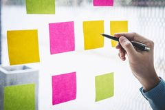 Note di Post-it di uso dell'uomo d'affari all'idea ed alla strategia di marketing di progettazione di affari, nota appiccicosa su immagine stock libera da diritti