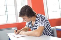Note di scrittura dell'allievo maschio in aula Fotografia Stock