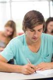 Note di scrittura dell'allievo maschio in aula Immagini Stock Libere da Diritti