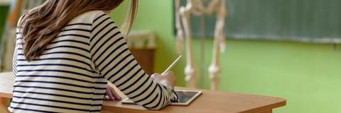 Note di scrittura della studentessa facendo uso della compressa digitale nella classe di Biologia Concetto di istruzione della ge fotografia stock