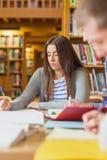 Note di scrittura dello studente allo scrittorio delle biblioteche Fotografie Stock