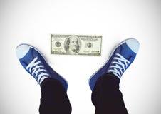 Note du dollar sur les chaussures moulues et bleues sur des pieds avec le fond blanc Photos libres de droits