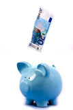 Note Falling into Blue Piggy Bank Royalty Free Stock Image