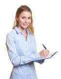 Note femminili attraenti di scrittura di segretario su una lavagna per appunti Fotografia Stock