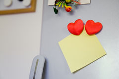 Note on the fridge. Blank yellow note with two hearts on the fridge Royalty Free Stock Photos