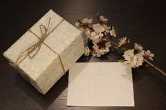Note, gift and blossom branch. A sheet of note paper, a gift and a flowering branch royalty free stock photo