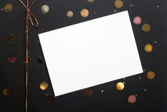 Note or greeting card, golden confetti and ribbon bow on black box background royalty free stock photography