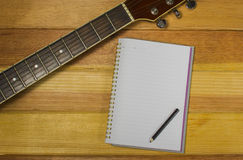 Note and guitar on the wooden. Floor Royalty Free Stock Images