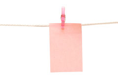 Note hanging on a rope. In isolated white background Royalty Free Stock Image