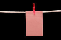 Note hanging on a rope. In isolated black background Royalty Free Stock Images