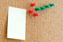 Note jaune avec des broches sur un tableau d'affichage Photographie stock libre de droits