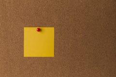 Note jaune collante sur la fin de panneau de liège  Image libre de droits