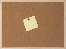 Note jaune collante sur le panneau de liège de cadre en bois Photos stock